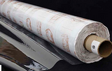 A partly unfurled roll of clear soft vinyl with white backing paper covered in brown motifs. The end of the roll has a label with a 6 on it.