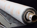 A partly unfurled roll of clear soft vinyl with white backing paper covered in orange motifs. The end of the roll has a label with a 8 on it.