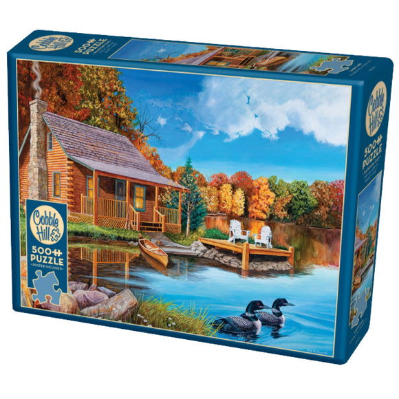 500 piece puzzle in packaging: Loon Lake (light wood log cabin on lake with dock and Muskoka chairs, 2 loons, blue sky)