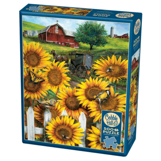 Cobble Hill 500pc puzzle - Country Paradise.  Image features large sunflowers with birds, bees and butterflies around a white picket fence in the foreground, and a horse and covered buggy in front of red barn in the distance.
