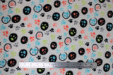 Flat swatch colourful paws white fabric (white fabric with small tossed paw prints in lime green, pale coral, blue, grey, black some plain, some with black circle outlines and some with solid black polka dot backgrounds)