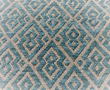 Turquoise-blue colourway of this jacquard geometric pattern with turquoise-blue in a velvety texture and cream for background. Pairs of joined diamonds resembling a mask are outlined by a second line of the same thickness