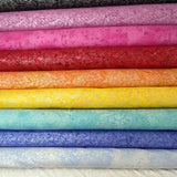 A stack of fabric bolts in a rainbow of solid shades, each covered with a shimmery silver frost pattern