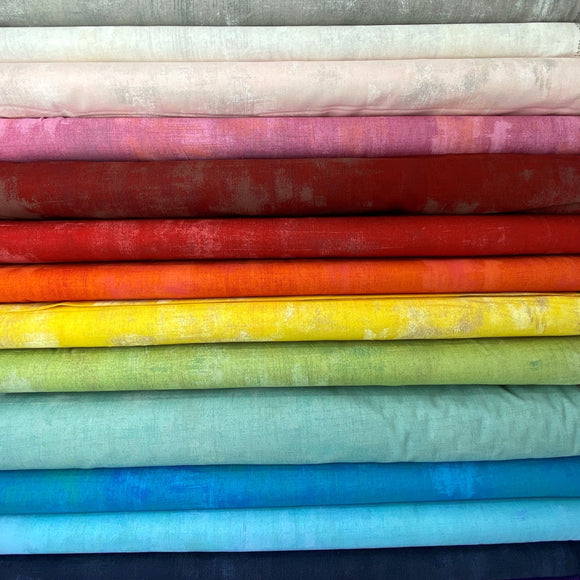A stack of fabric bolts in a rainbow of colours, each with a faded or distressed grunge pattern.
