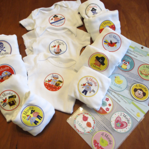 An arrangement of infant shirts and diapers displaying monthly iron-on badges