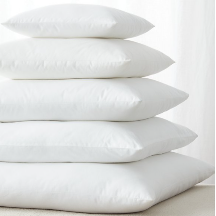A stack of square, white cushions in decreasing sizes, each centred on the one below it.