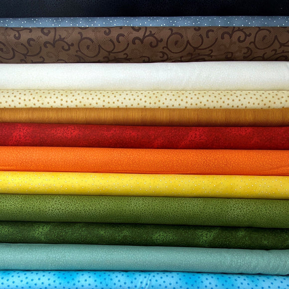 A stack of fabric bolts featuring micro prints in a variety of colours
