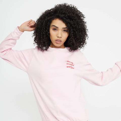 Feminist slogan pink sweatshirt with red embroidered 'Does my sassiness upset you?' quote from Maya Angelou Still I Rise poem