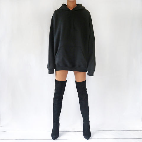 Black oversized plain hoodie dress for women paired with knee high boots. Available in sizes S,M,L.