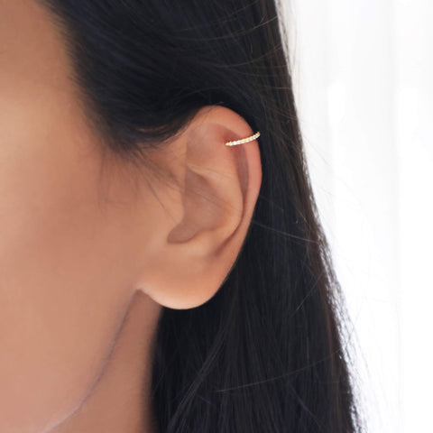 Closeup of a woman's ear with a gold cubic zirconia ear cuff clipped on to the top of the ear