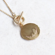 Gold disc pendant necklace with a gold chain and bar toggle clasp with 'trust the timing' engraved, on a marble background.