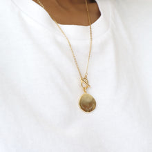 Woman wearing a gold disc pendant necklace with a gold chain and bar toggle clasp with 'trust the timing' engraved.