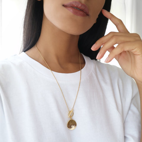 Woman in a white t-shirt wearing a gold disc necklace with a gold chain and bar toggle clasp with 'trust the timing' engraved