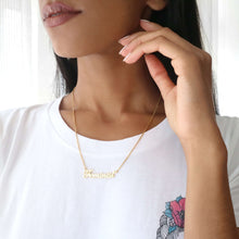 Woman wearing gold feminist script name necklace with frida kahlo feminist t-shirt.