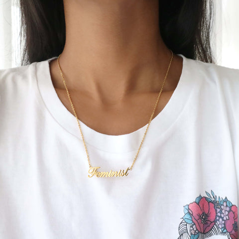 Woman wearing gold feminist script name necklace with frida kahlo feminist t-shirt