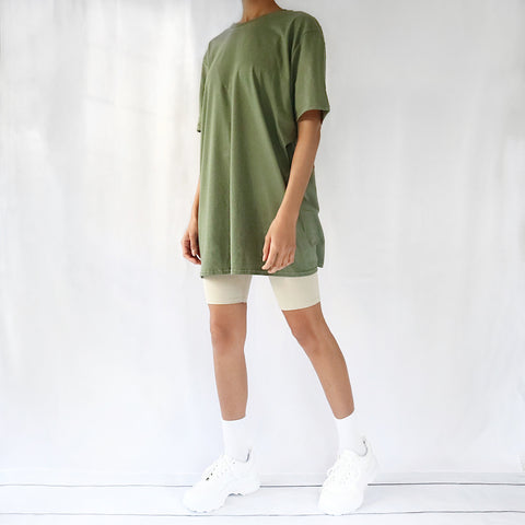 Khaki green oversized plain t-shirt dress for women paired with cream cycling shorts and chunky trainers. Casual 90s outfit.