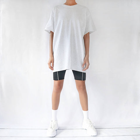 Light grey oversized plain t-shirt dress for women paired with black cycling shorts and chunky trainers. Casual 90s outfit.