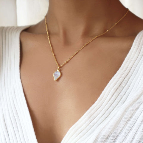 Women wearing moonstone pendant necklace with gold satellite chain, by Rani & Co.