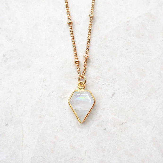 Moonstone rainbow pendant necklace with gold satellite chain on marble background, by Rani & Co.