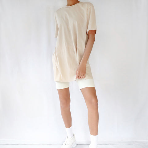 Sand camel beige nude oversized plain t-shirt dress for women paired with cream cycling shorts and chunky trainers.