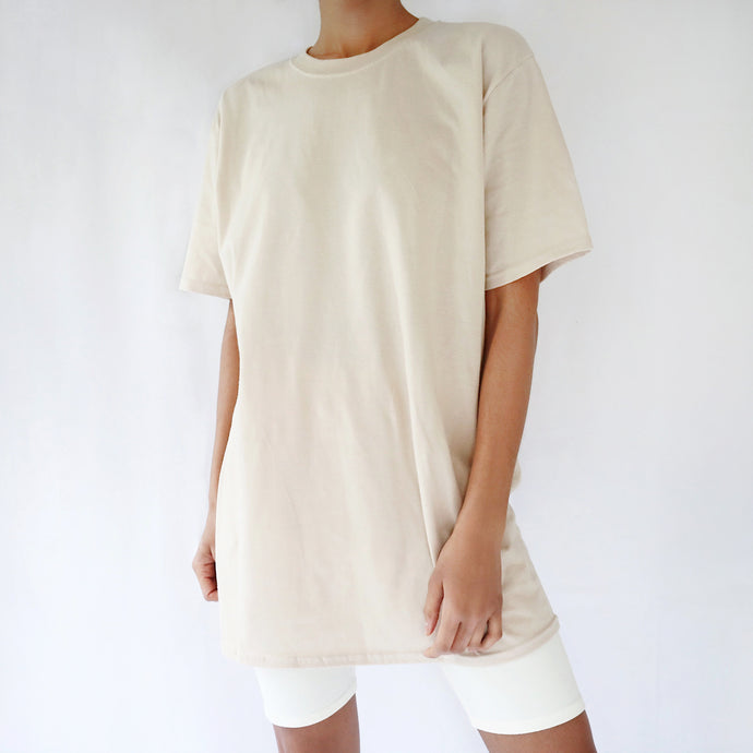 Sand camel beige oversized plain t-shirt dress for women paired with cream cycling shorts. Ethical t-shirt.