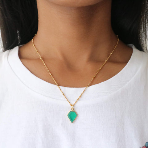Close up of a woman wearing a diamond shaped green onyx stone necklace in an 18k gold-plated frame, with a gold satellite chain.