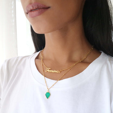 Close up of a woman wearing a gold and diamond shaped green onyx stone necklace with a gold feminist necklace.