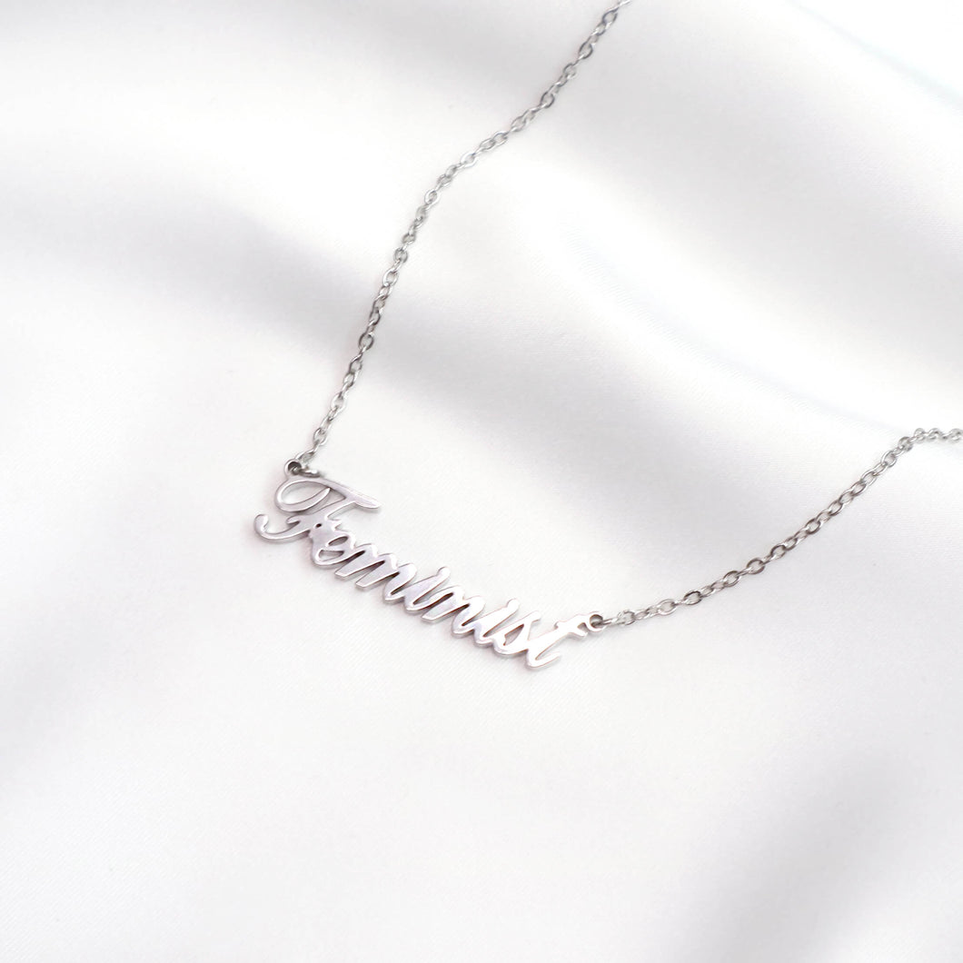 Silver feminist word necklace on silk background, by feminist brand Rani & Co.