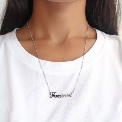 Woman wearing silver feminist script name necklace with white t-shirt.