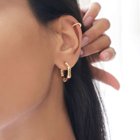 Closeup of a woman's ear with a gold cubic zirconia ear cuff and gold bamboo hoop earring