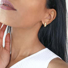 Woman wearing small thick gold hoop earrings with 3 cubic zirconia stars. 18k gold-plated copper.