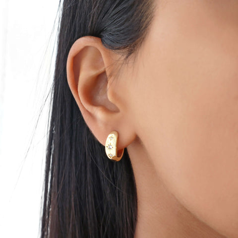Dainty minimal small thick gold hoop earrings with 3 cubic zirconia stars. 18k gold-plated copper.