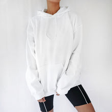White oversized plain hoodie dress for women paired with black cycling shorts. Casual 90s outfit.