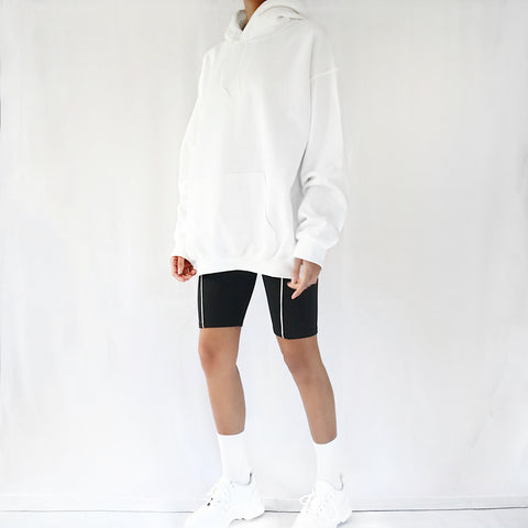 White oversized plain hoodie dress for women paired with black cycling shorts and chunky trainers. Ethically made hoodie.