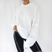 White oversized plain hoodie dress for women paired with black cycling shorts. Trendy 90s outfit.