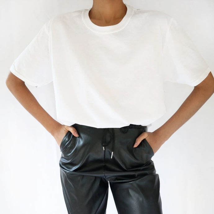 White oversized plain t-shirt dress for women paired with black leather trousers. Ethical vegan t-shirt.