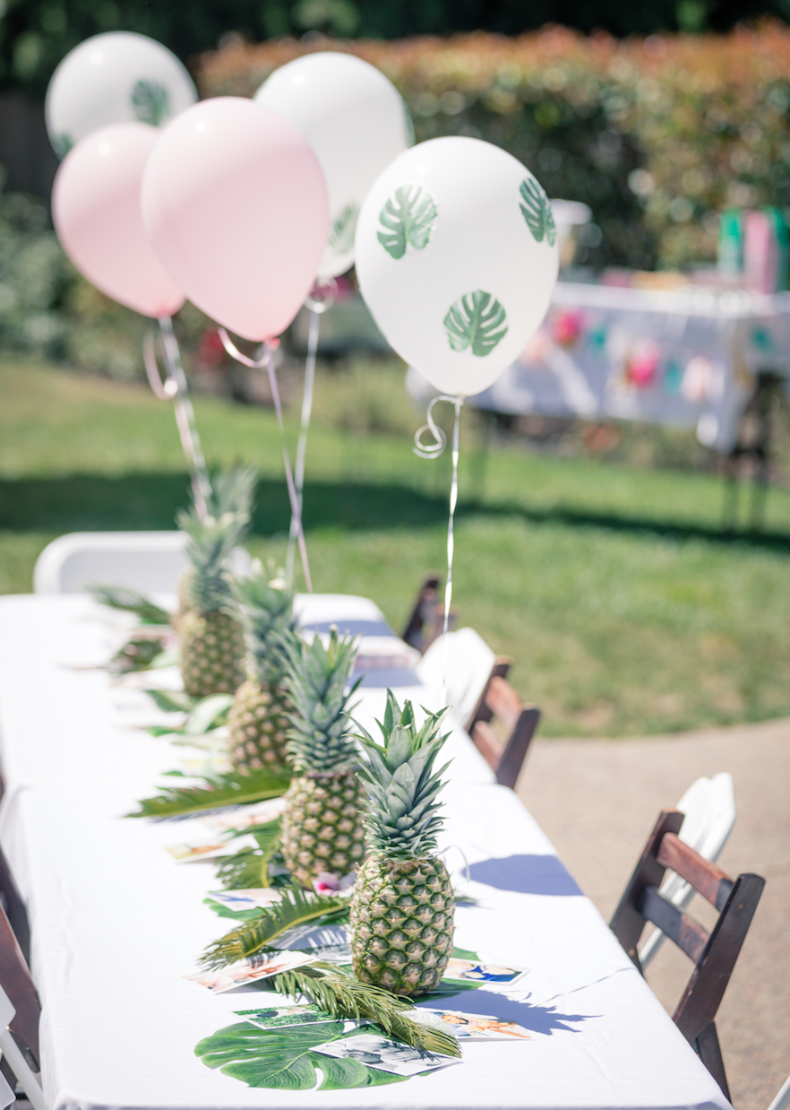 long table with palm fronds and balloons standing on the table