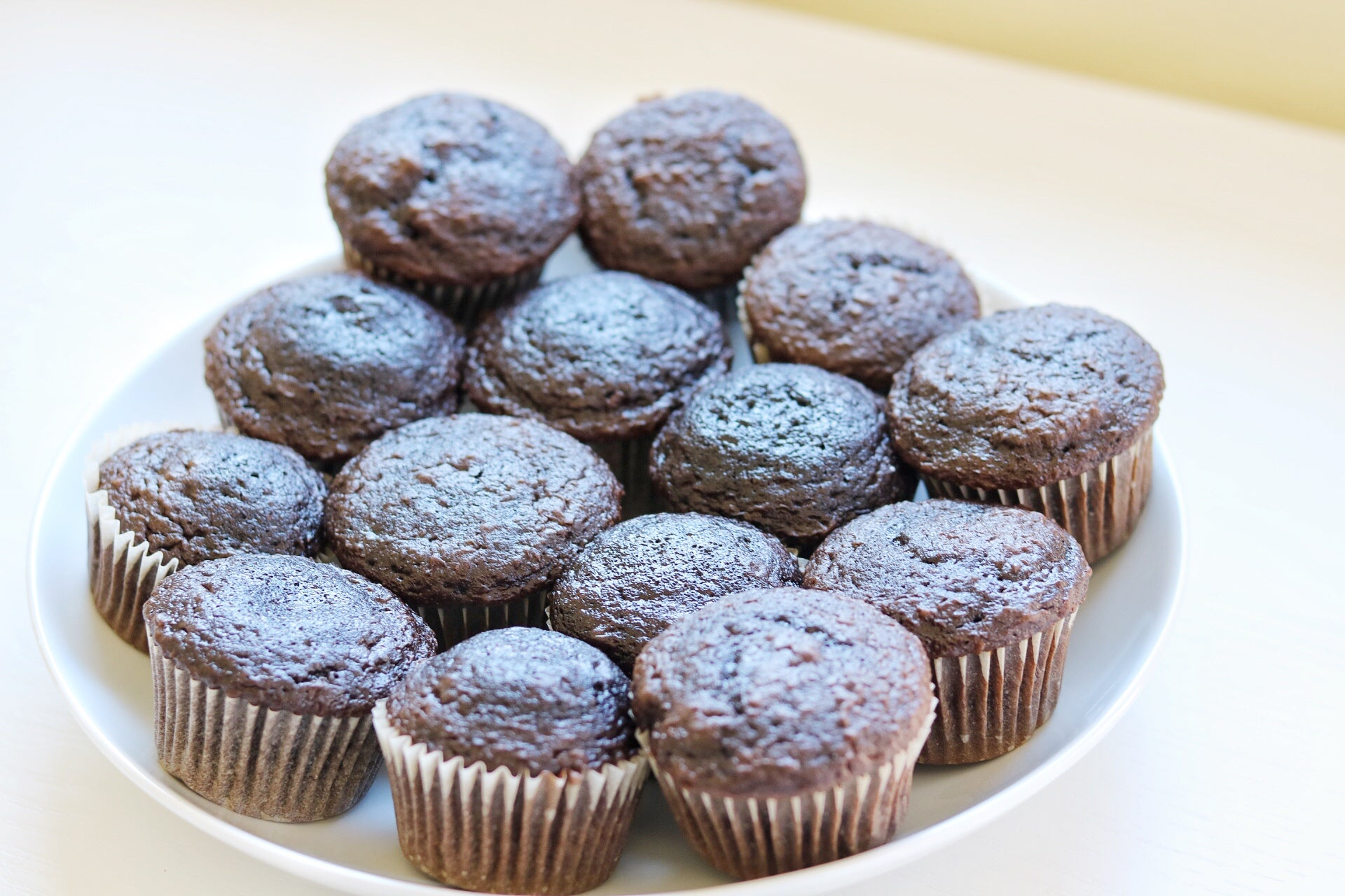 plate of unfrosted baked chocolate cupcakes