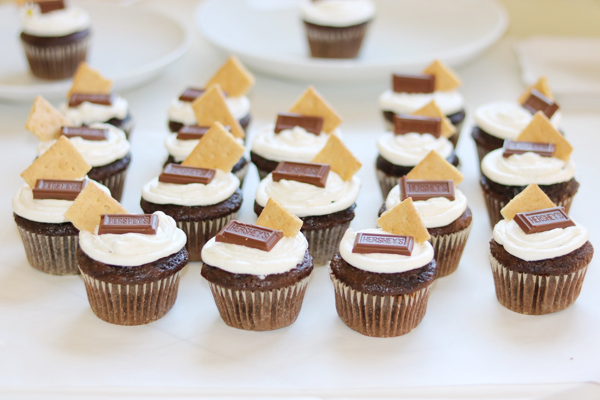 chocolate cupcakes with marshmallow frosting topped with a graham cracker square and hershey's chocolate