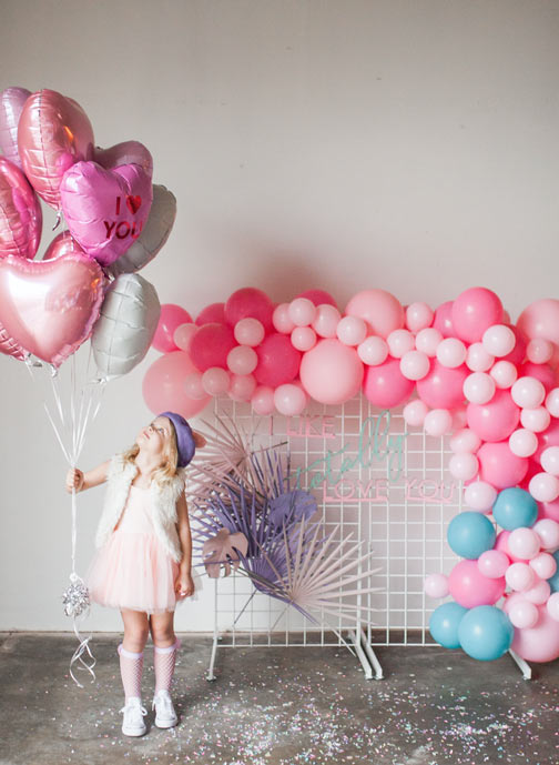 cute little girl holding balloons