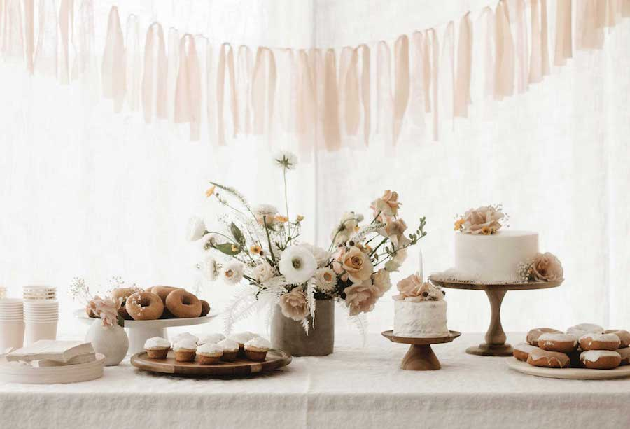 light pink party table setup with flowers and cake