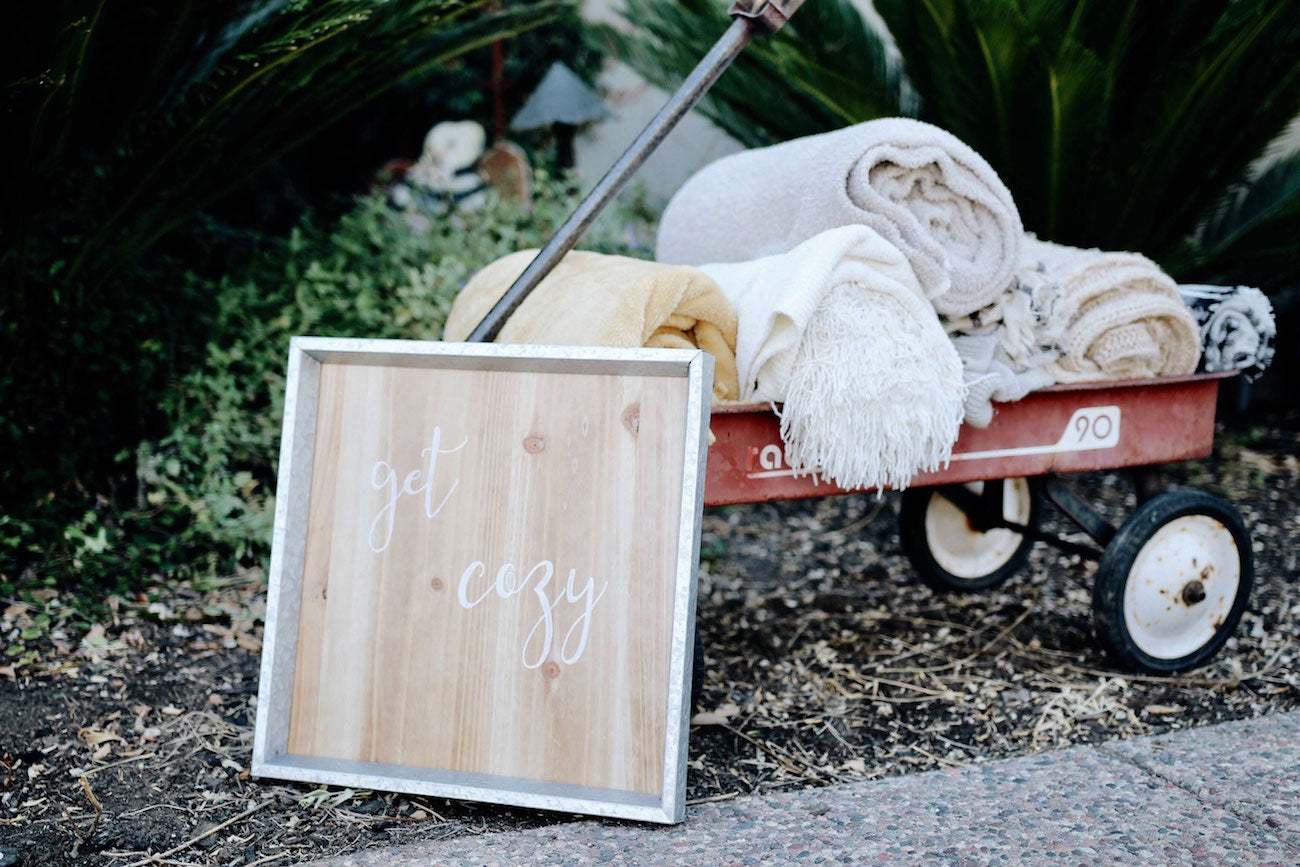 cozy up sign leaning agains a wagon of blankets