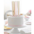 birthday cake with pink, gold and white tall cake candles