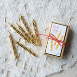 a box of gold cake candles with sparkles