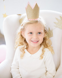 little girl sitting on a chair smiling wearing a party crown