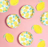 lemon party napkins and plates spread on pink table