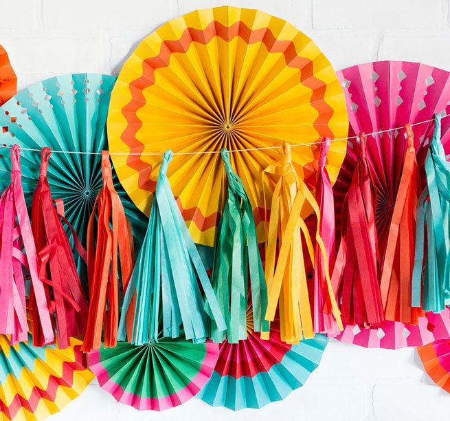 colorful fiesta tassels hung on a wall with party fans