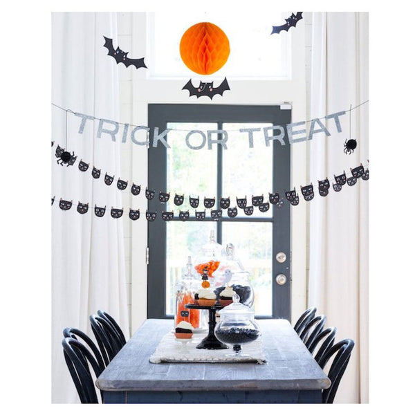 Trick or Treat Banner hanging above a table dressed for halloween