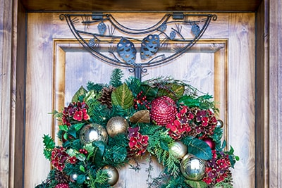 Village Lighting Wreath Hanger on door with scarlet hydrangea wreath