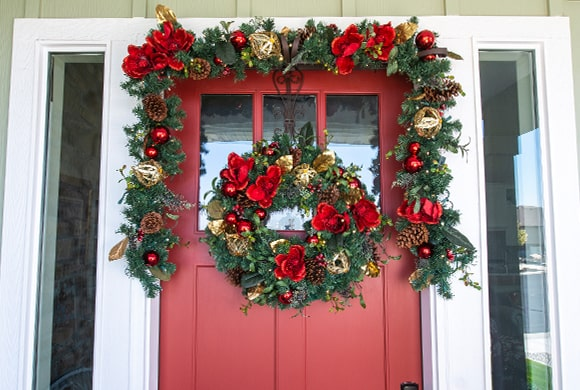Red Magnolia Wreath and Garland Hanging On Front Door